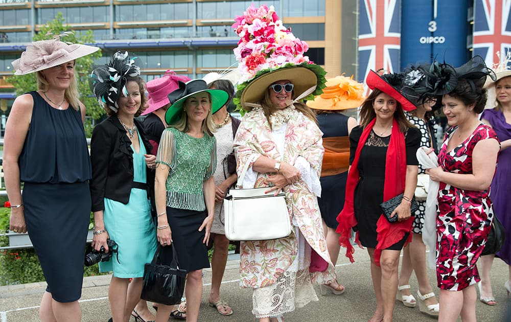 Paula Iachetti, centre, poses with a group of women for photographers on the third day of the Royal Ascot horse racing meeting, which is traditionally known as Ladies Day, at Ascot, England.