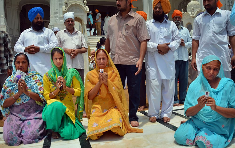 Family members pray for the safety of their missing sons as they display their photographs during their visit to the Golden Temple, Sikh's holiest temple, in Amritsar.