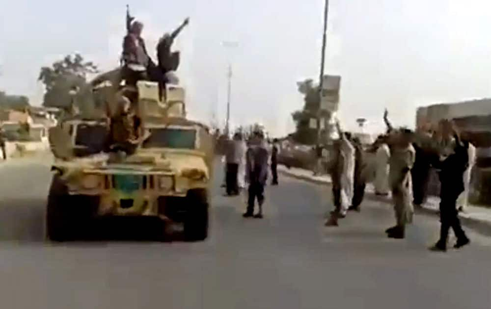 In this Tuesday, June 17, 2014 image taken from video uploaded to a militant social media account, which has been authenticated based on its contents and other AP reporting, al-Qaida-inspired Islamic State of Iraq and the Levant militants raise their weapons as they arrive to the country's largest oil refinery in Beiji, some 250 kilometers (155 miles) north of the capital, Baghdad, Iraq.