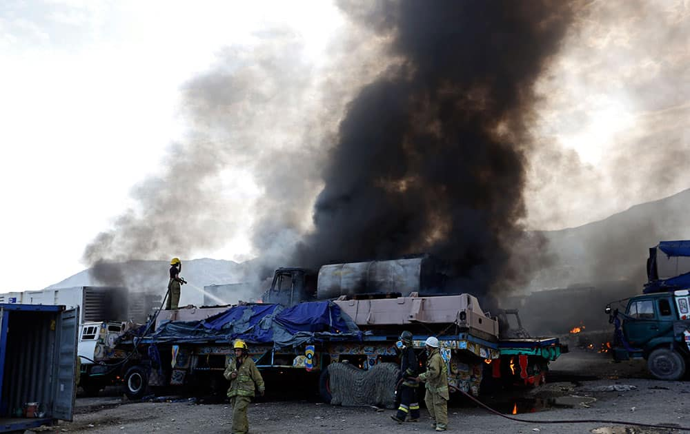 Firefighters work near the scene of an attack in Torkham, Nangarhar province, Afghanistan. Afghan officials say three Taliban suicide bombers targeted NATO fuel trucks at the border with Pakistan, setting off a gunbattle with police guards