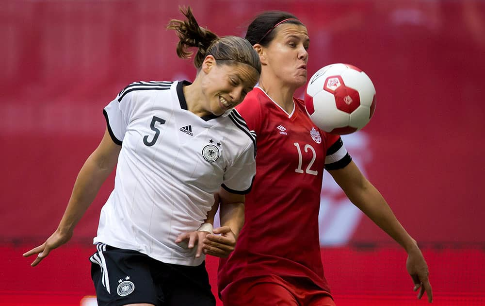 Germany`s Annike Krahn, left, and Canada`s Christine Sinclair vie for the ball during the first half of an international women`s soccer game in Vancouver, British Columbia.
