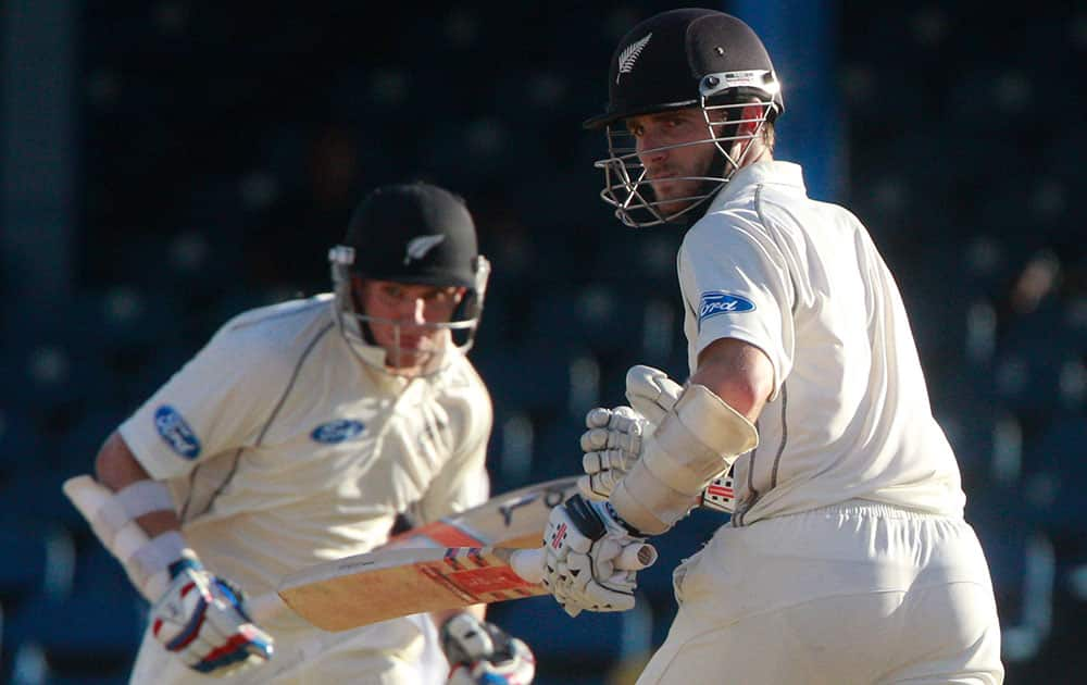 New Zealand batsmen Kane Williamson, right, and Tom Latham run between the wickets during the second innings on the third day of their second cricket Test match against West Indies in Port of Spain, Trinidad.
