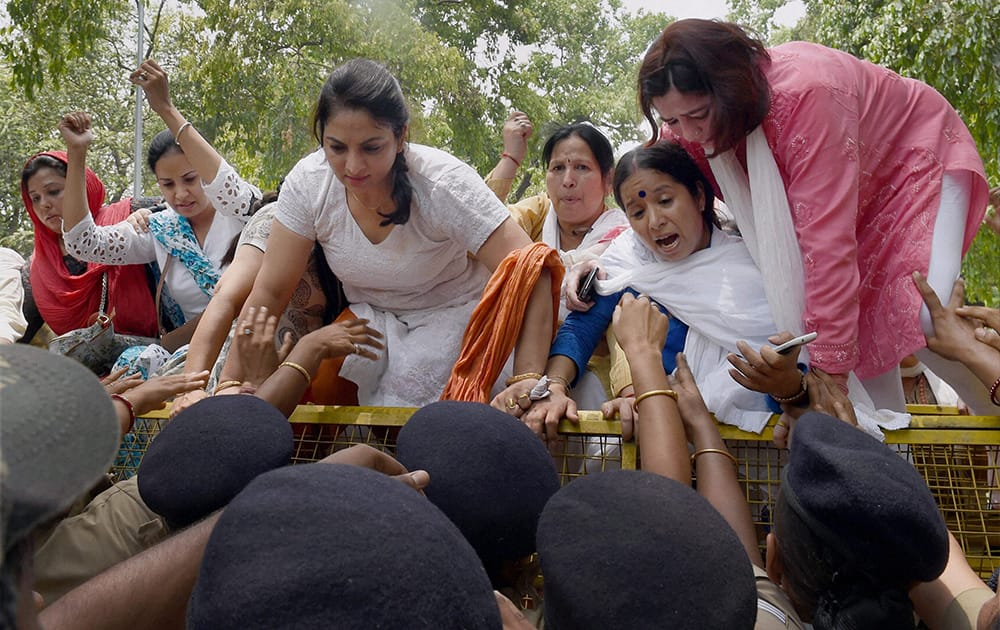 Women Congress workers try to break a barricade during a protest demanding resignation of Minister of State Nihal Chand in New Delhi.