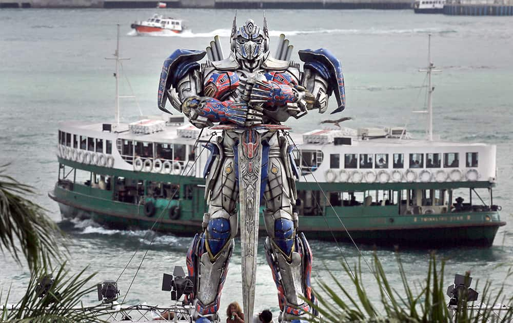 A ferry sails past a giant Transformer figure which is displayed against Victoria Habour in Hong Kong. World premiere of the movie Transformer is slated for Thursday in Hong Kong.
