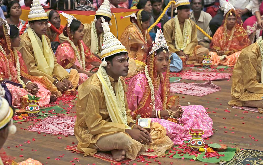 Brides and grooms sit together during a mass wedding organized by a social organization for sixty-five couple belonging to socially and economically backward communities in Kolkata.
