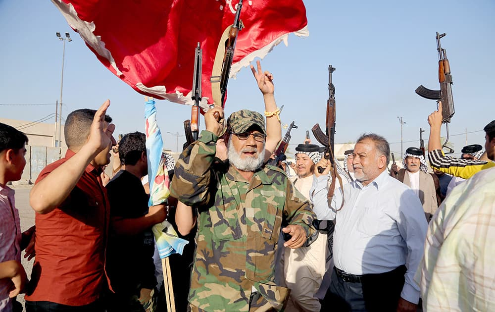 Iraqi Shiite tribal fighters raise their weapons and chant slogans against the al-Qaida-inspired Islamic State of Iraq and the Levant, after authorities urged Iraqis to help battle insurgents, in Baghdad`s Sadr city, Iraq.