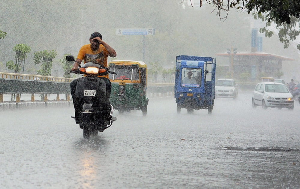 People commute in heavy rains in Ahmedabad.