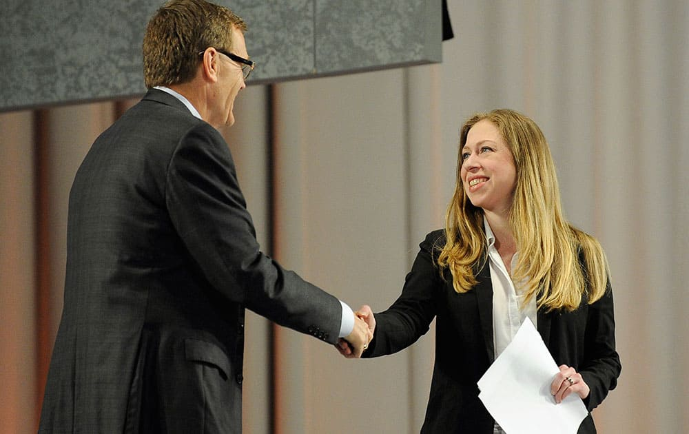Chelsea Clinton, right, is introduced by UPS CEO-elect David Abney, left, at the opening plenary session for the `Service Unites` conference sponsored by the Points of Light Foundation, in Atlanta. Clinton called for more opportunities to engage millennials in community service during her speech.