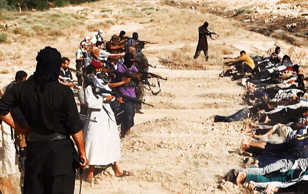 This image posted on a militant website on Saturday, June 14, 2014, which has been verified and is consistent with other AP reporting, appears to show militants from the al-Qaida-inspired Islamic State of Iraq and the Levant (ISIL) taking aim at captured Iraqi soldiers wearing plain clothes after taking over a base in Tikrit, Iraq.