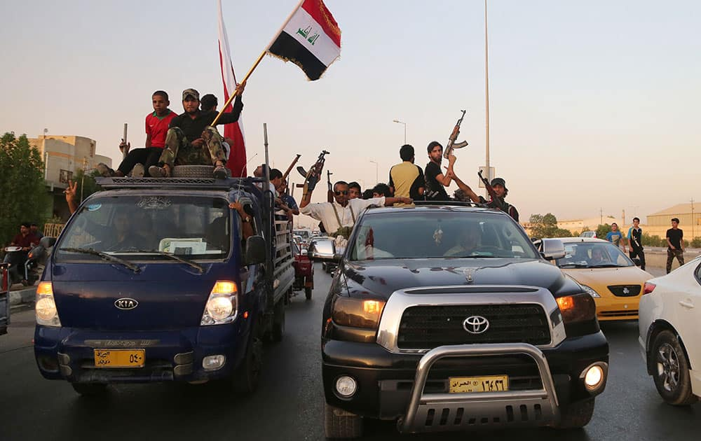 Shiite tribal fighters raise their weapons and chant slogans against the al-Qaida-inspired Islamic State of Iraq and the Levant (ISIL) in Basra, Iraq`s second-largest city, 340 miles (550 kilometers) southeast of Baghdad, Iraq.