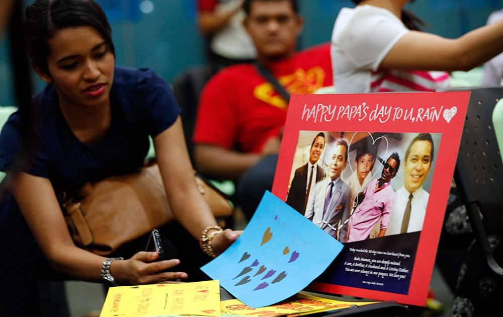 A relative of one of Malaysian passengers on board the missing Malaysia Airlines Flight 370 looks at a picture of missing crew during an event to commemorate the 100th day after the flight went missing, in Kuala Lumpur.