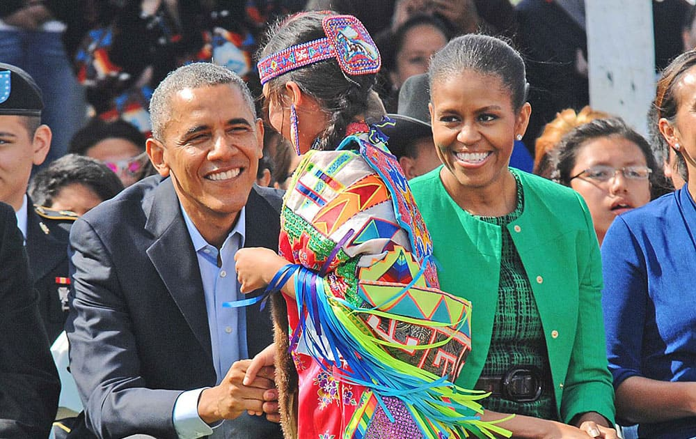 President Barack Obama and first lady Michelle Obama greet a young dancer after an honoring song inside the Cannon Ball, ND, community pow wow arbor. Obama on Friday became only the third US sitting president in eight decades to set foot in Indian Country, encountering both the wonder of Native American culture and the struggle of tribal life on a breeze-whipped afternoon in the prairie.