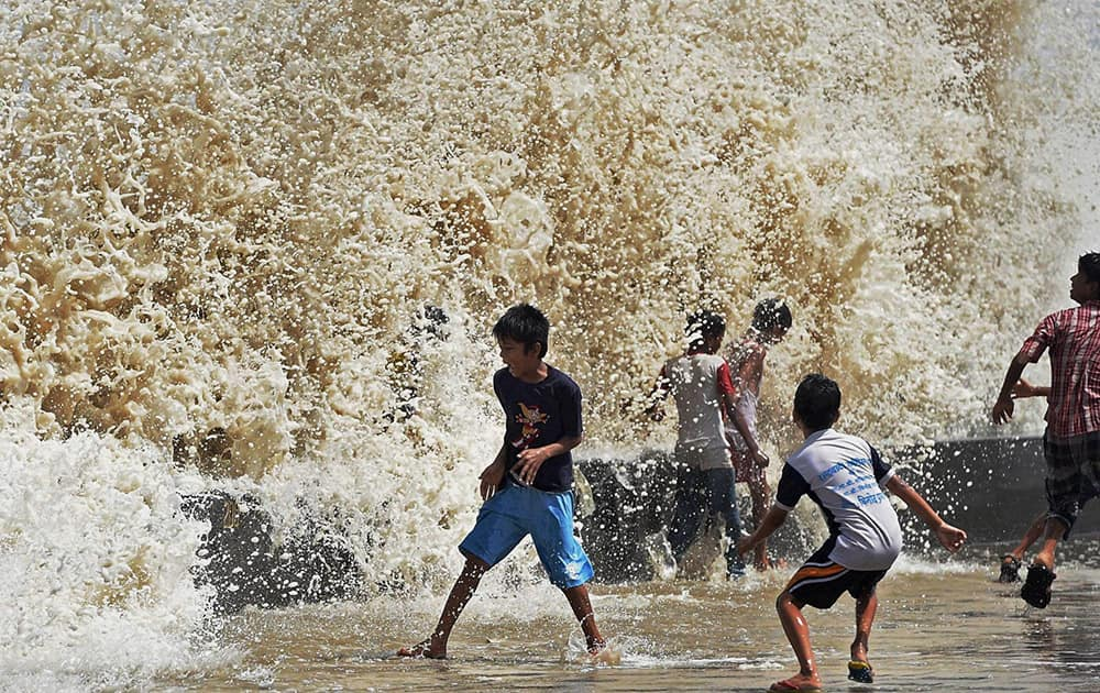 Children enjoy a high tide at Worli seaface in Mumbai.