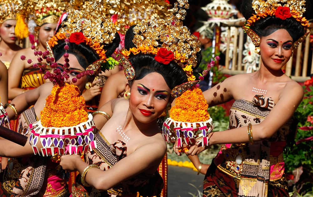 Indonesian dancers in traditional outfit perform during a parade to mark the Bali Arts Festival in Bali, Indonesia.