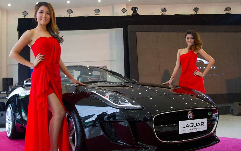 Myanmar models pose for photos by a Jaguar model during a launch ceremony of Jaguar Land Rover Motor Company Showroom in Yangon, Myanmar.