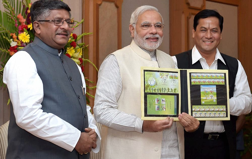 Prime Minister Narendra Modi with Communication and IT Minister Ravi Shanker Prasad and Sports Minister Sarbananda Sonowal releases commemorative postage stamps on the 2014 FIFA World Cup, in New Delhi.