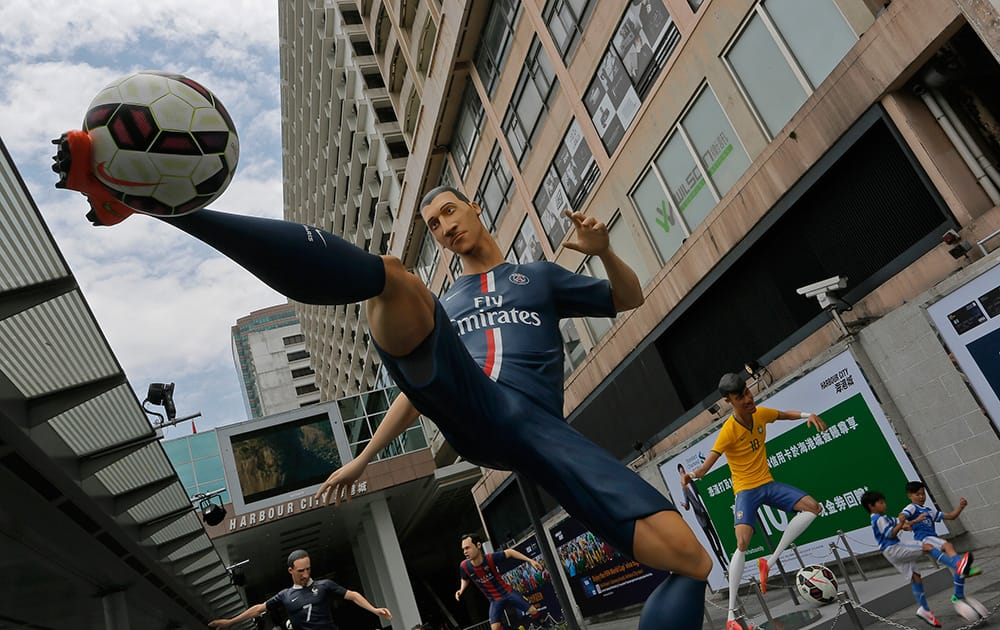 Giant size figures of Swedish striker Zlatan Ibrahimovic, left, and Brazilian striker Neymar, right, are displayed outside a shopping mall in Hong Kong.