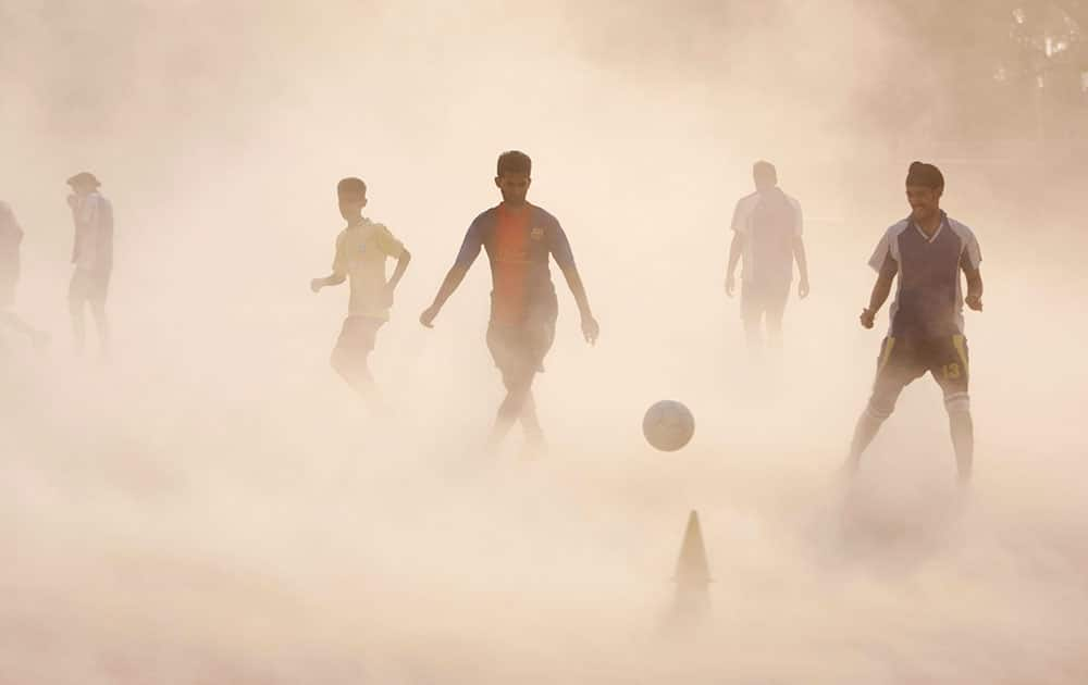 10ThingstoSeeSports - Aspiring young Indian soccer players continue with their practice during a dust storm in Jammu, India.
