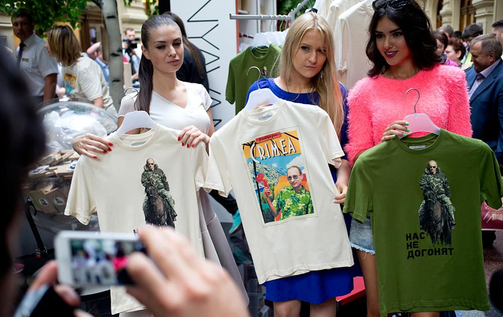 Models display T-shirts depicting Russian President Vladimir Putin and the one in center reads Greetings from Crimea at the biggest department store GUM in Moscow`s Red Square.