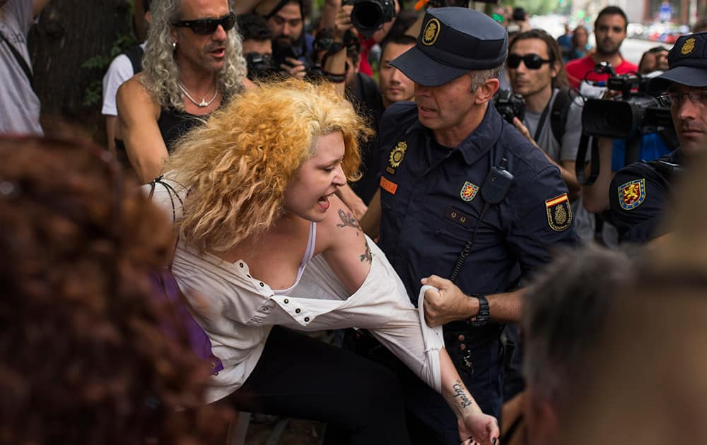 A riot police officer grabs a protestor who was shouting slogans against the monarchy, during a protest against the Monarchy near the parliament in Madrid, Spain.