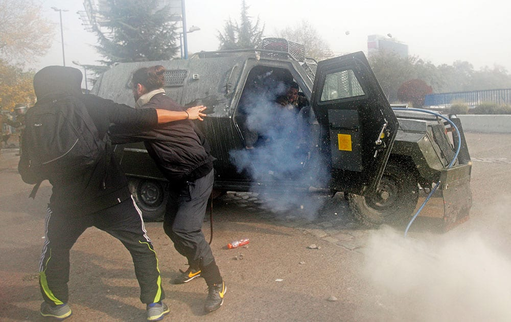A police officer, is attacked by protesters after he opened the door of his armored car to throw a tear gas grenade in the courtyard of the University of Santiago, in Santiago, Chile.