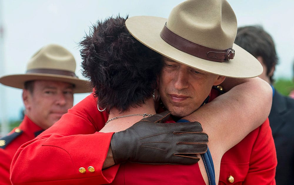 An officer is embraced at the end of the regimental funeral for the three Royal Canadian Mounted Police officers, who were killed on duty, at the Moncton Coliseum in Moncton, New Brunswick.