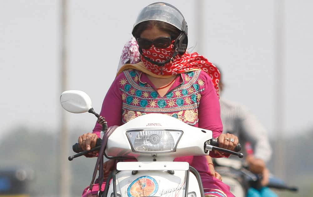 A woman shields her face with a piece of cloth to protect from the heat, as she rides a two wheeler on a hot summer day in Jammu.