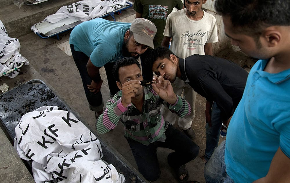 Pakistani family members try to read a burned identity card recovered from a victim of a deadly Taliban attack on Jinnah International Airport, last Sunday, in Karachi.