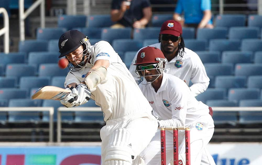 New Zealand`s batsman Tim Southee, left, drives for a six as West Indies wicket keeper Denesh Ramdin, center, and Chris Gayle, right back, looks on during the second day of their first cricket Test match in Kingston, Jamaica.
