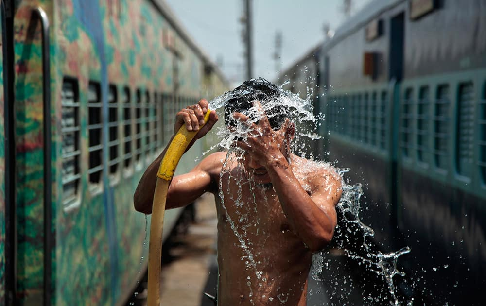 A man takes a shower at a railway station to cool himself down in Jammu.