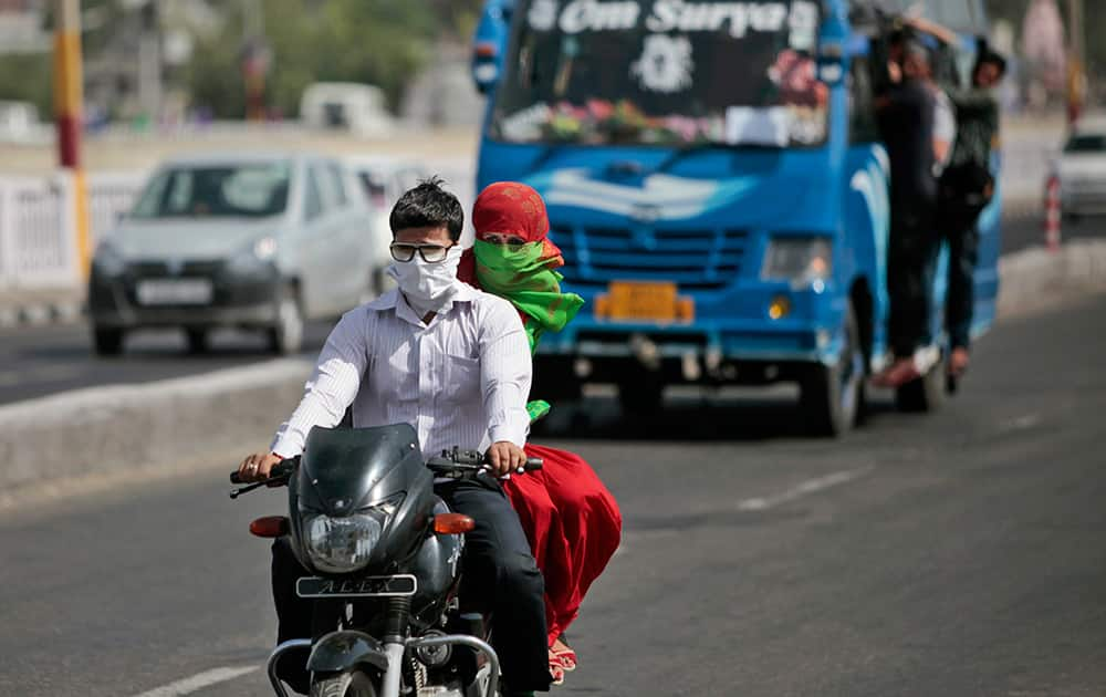 Commuters have their faces covered with scarves to keep from the heat as they ride on a motorbike in Jammu.
