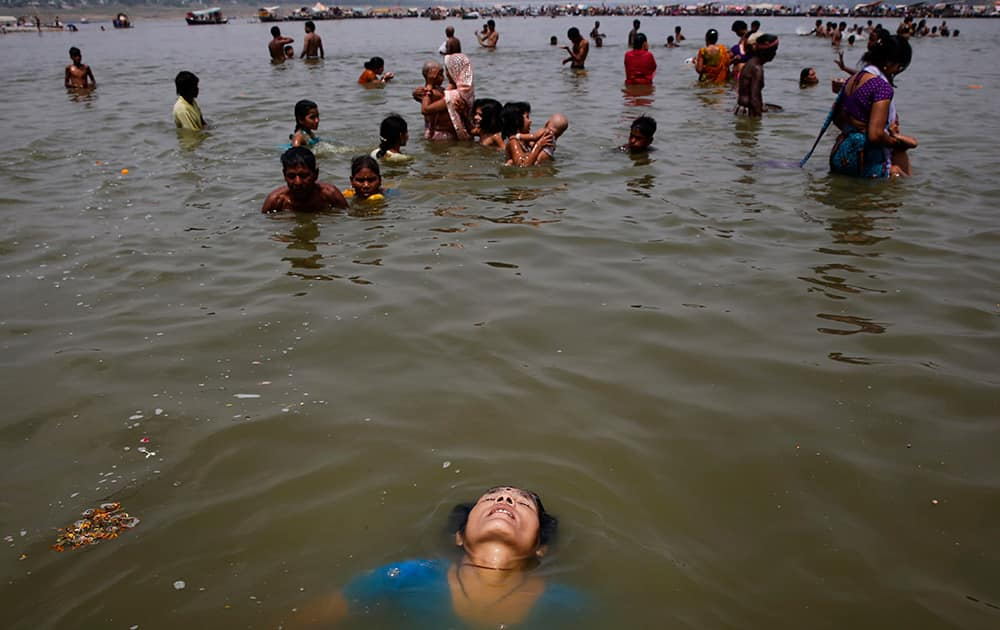A woman bathes in the river Ganges on a hot summer afternoon in Allahabad.