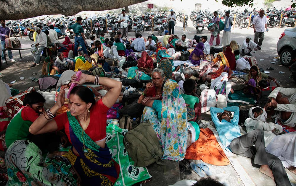 Hindu pilgrims on their way to the Vaishno Devi shrine, rest under the shade of trees outside a railway station in Jammu.
