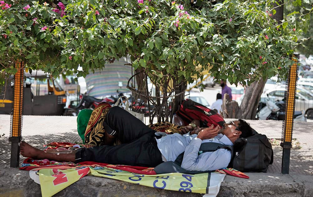 A pilgrim on his way to the Vaishno Devi shrine rests under the shade of a tree outside a railway station in Jammu.