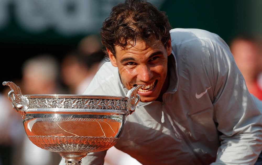 Spain`s Rafael Nadal bites the trophy after winning the final of the French Open tennis tournament against Serbia`s Novak Djokovic at the Roland Garros stadium, in Paris.