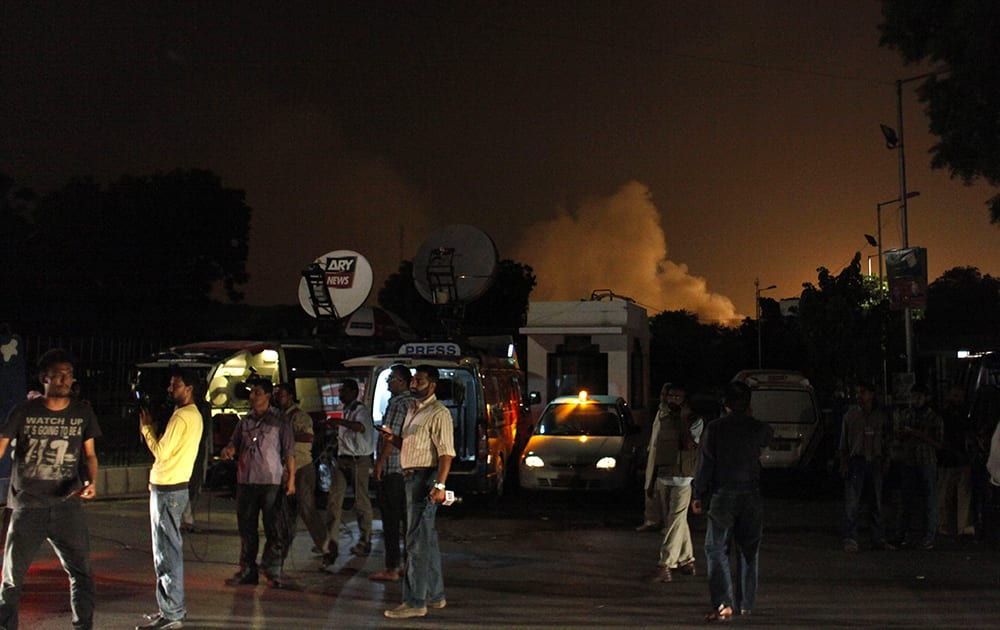 Reporters stand outside the Karachi airport terminal where security forces are fighting with attackers in Pakistan.