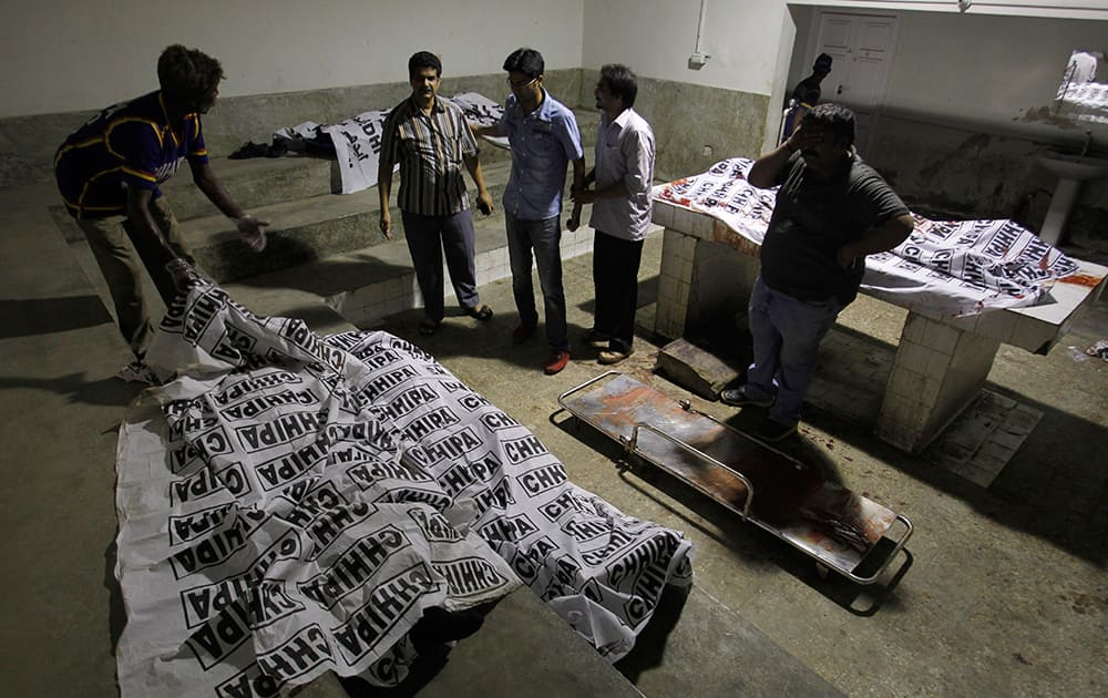 Volunteers look at dead bodies of people killed during an attack by unknown gunmen on Jinnah International Airport, in Karachi, Pakistan.