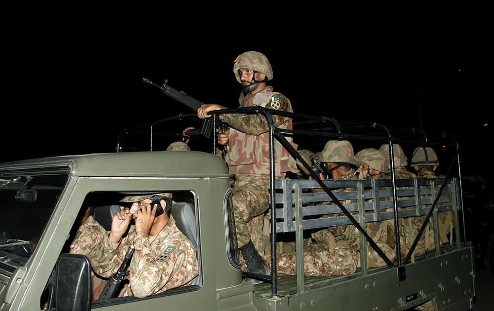 Pakistani troops arrive at Jinnah International Airport following an attack by unknown gunmen disguised as police guards who stormed a terminal used for VIPs and cargo, in Karachi, Pakistan.