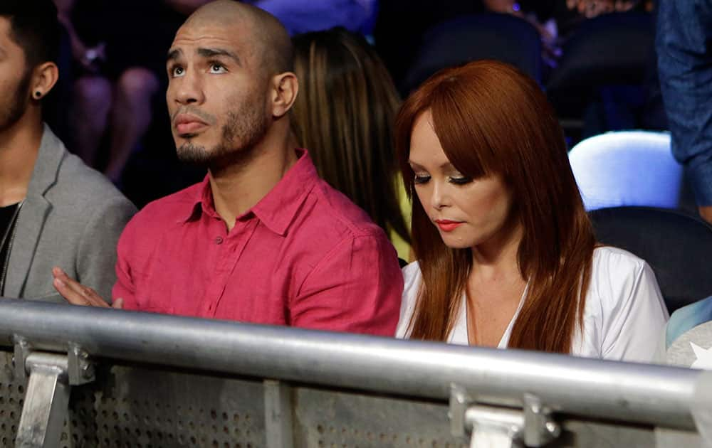 Miguel Cotto, of Puerto Rico, left, watches an undercard fight with his wife Melissa Guzman Cotto, right, before an upcoming fight with Sergio Martinez, of Argentina.