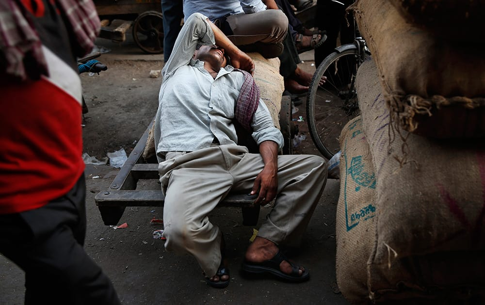 A laborer catches up on his sleep as he waits for his next delivery assignment at a wholesale market on a hot summer afternoon in New Delhi.