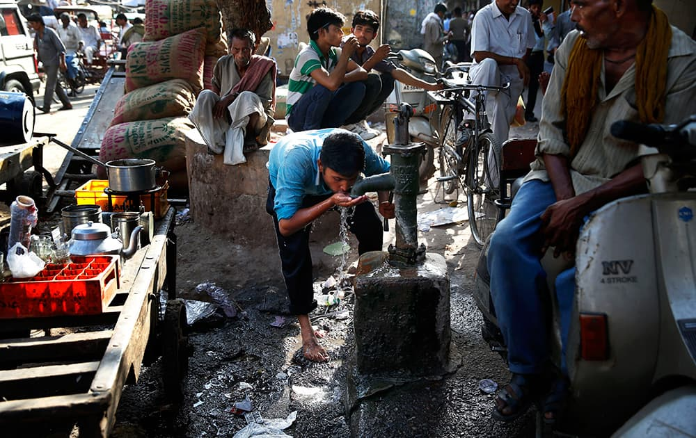 A laborer quenches his thirst from a roadside tube well at a wholesale market on a hot summer afternoon in New Delhi.