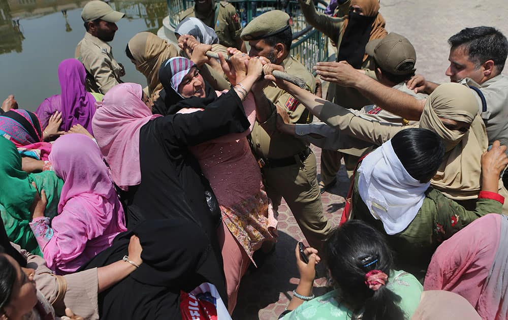 Workers of Anganwadi, a government sponsored child and mother care, scuffles with Indian police trying to stop them marching forward during a protest in Srinagar.