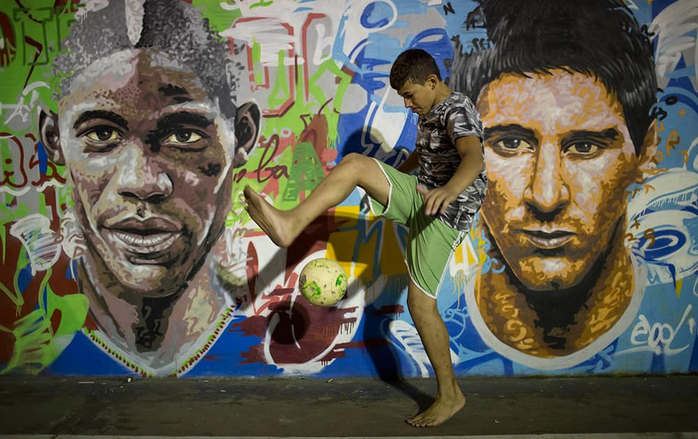 A boy practices freestyle soccer next to a mural depicting soccer players Italy`s Mario Balotelli and Argentina`s Lionel Messi at a slum in Rio de Janeiro, Brazil.