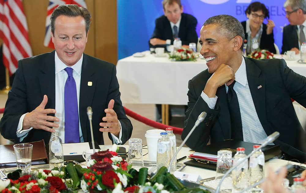US President Barack Obama, smiles as he listens to British Prime Minister David Cameron, during a G7 working session in Brussels, Belgium.