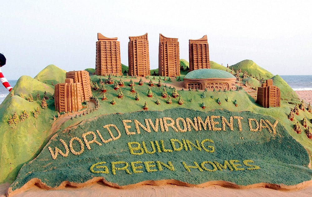 Sand artist Sudarsan Pattnaik creates a sand sculpture on World Environment Day at Puri beach in Odisha.