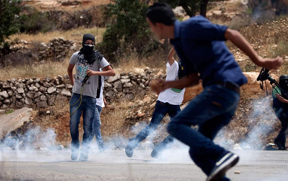 Palestinians run from tear gas during clashes with Israeli soldiers after a protest in support of Palestinian prisoners hunger striking since 42 days in Israeli jails, outside Ofer, an Israeli military prison near the West Bank city of Ramallah.