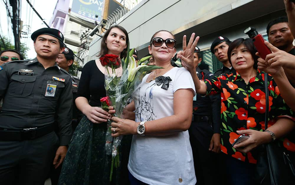 An unidentified Australian Embassy official, center left, receives a bouquet of flowers from a protester, center right, as another gestures beside her, during an anti-coup demonstration outside the Australian Embassy in Bangkok, Thailand.