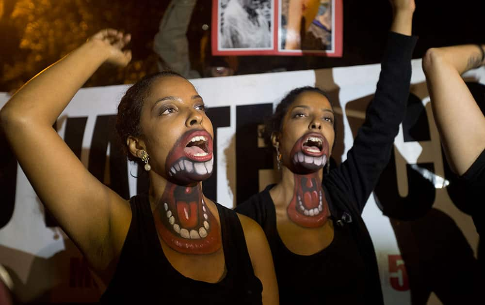 Women protest with mouths painted on them, demanding better salaries and labor conditions in Rio de Janeiro, Brazil.