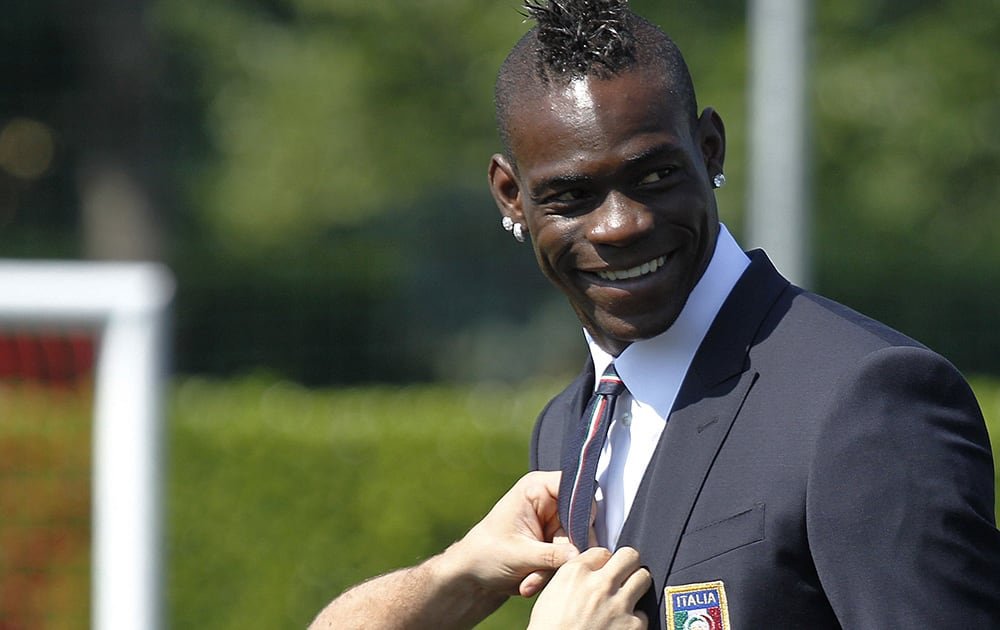 Italy forward Mario Balotelli has his tie adjusted at the Coverciano center, near Florence, Italy.