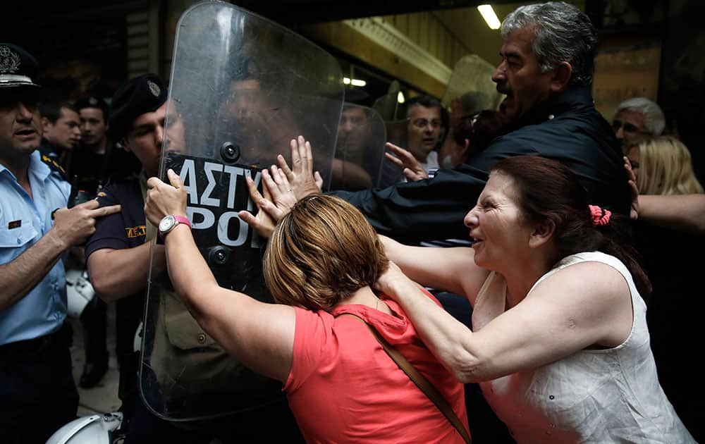 Protesting former Finance Ministry cleaning staff, who lost their jobs last year, scuffle with riot police outside a Finance Ministry building in central Athens.